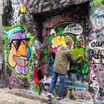 A man graffiti-ing in broad daylight